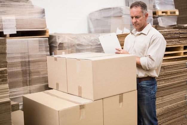 Trabajador de almacén revisando su lista en el portapapeles