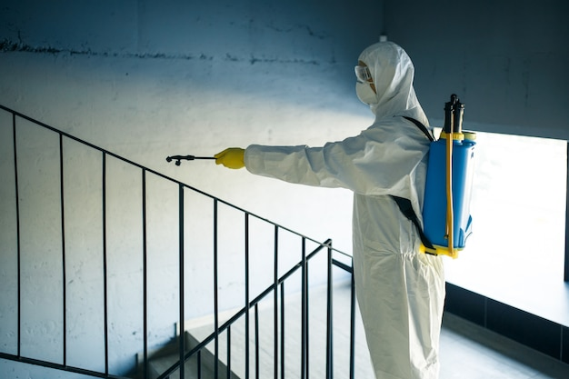 Trabajador de desinfección que limpia la escalera en el centro comercial con un antiséptico para evitar la propagación del covid-19. un hombre con un traje de desinfección rocía escaleras.