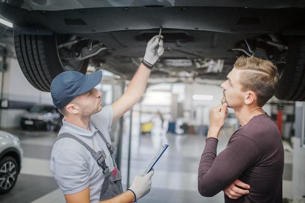 El trabajador y el dueño se encuentran debajo del automóvil. el primer hombre es el punto en el vehículo. otro está pensando.