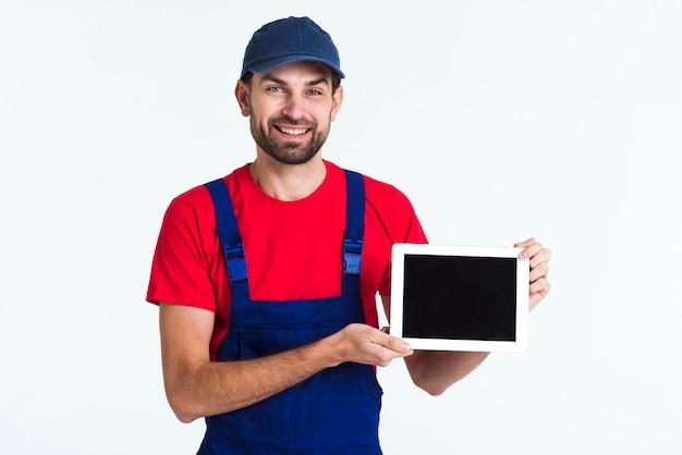 Trabajador duro mensajero hombre sosteniendo una tableta de tiro medio