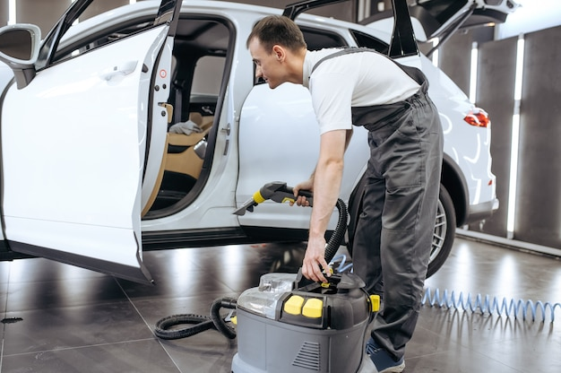 El trabajador elimina la suciedad con una aspiradora, limpieza en seco de automóviles y detalles.