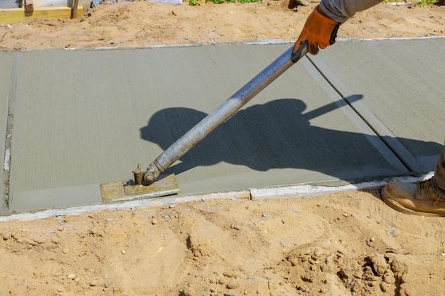 Trabajador enlucido del cemento concreto durante la acera