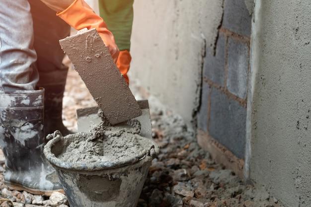 Trabajador enlucido de cemento en la pared para construir casa