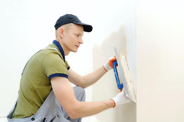 Trabajador enlucido de una pared en un apartamento con una paleta larga