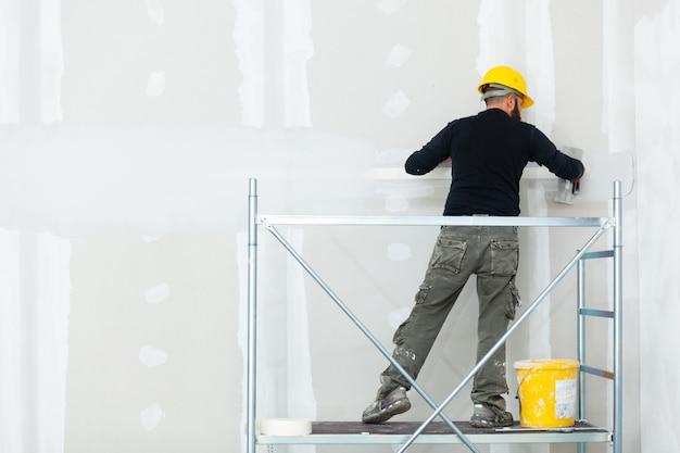 Trabajador enlucido de pared de tablero de yeso.