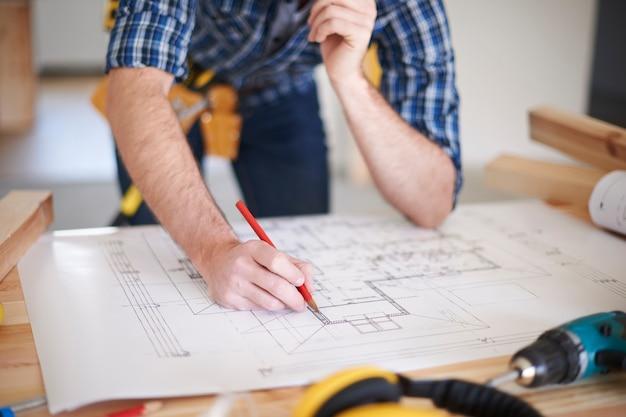 Trabajador con enmiendas sobre planos de casa