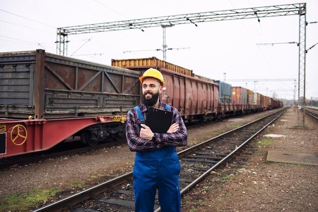 Trabajador de envío mirando el tren que llega a la estación y organizando la distribución y exportación de mercancías