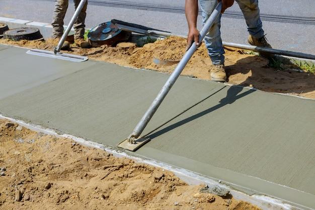 Trabajador enyesado del cemento de hormigón durante la acera
