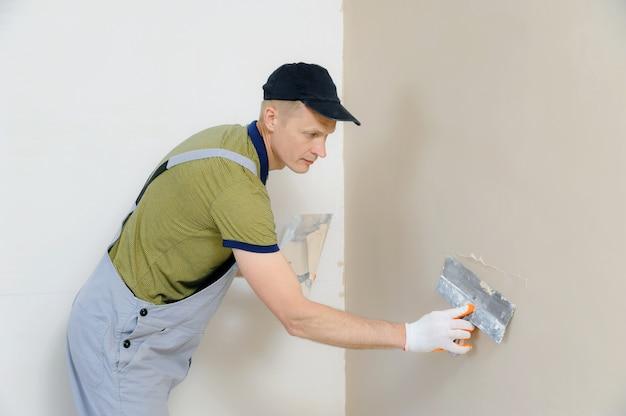 Un trabajador está enyesando una pared.