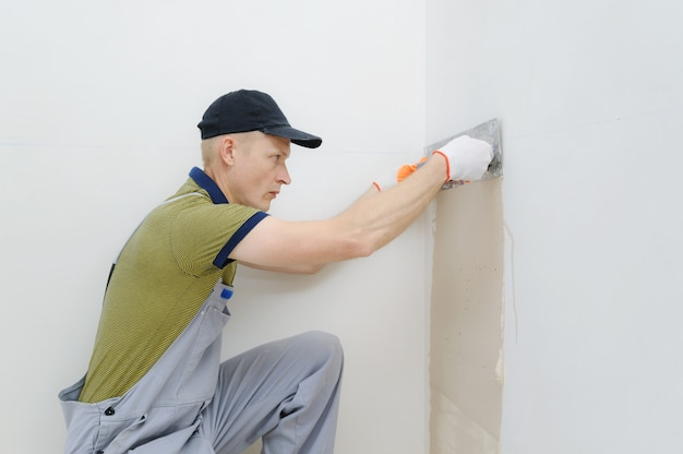Un trabajador enyesando una pared.