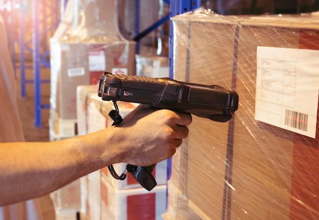 Trabajador de escaneo de escáner de código de barras en los productos en el almacén.