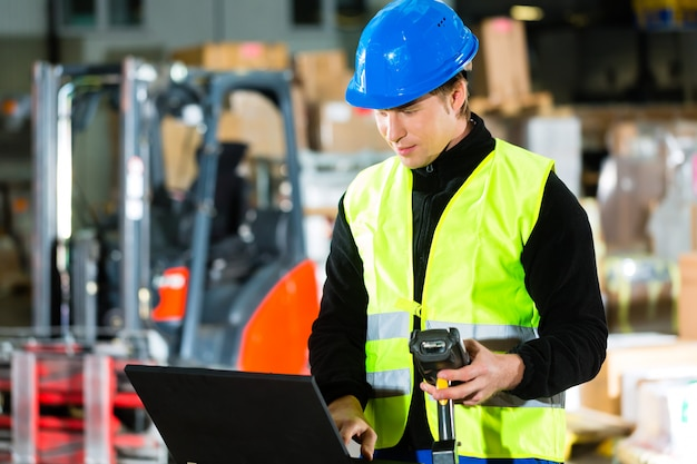 Trabajador con escáner y computadora portátil en el reenvío