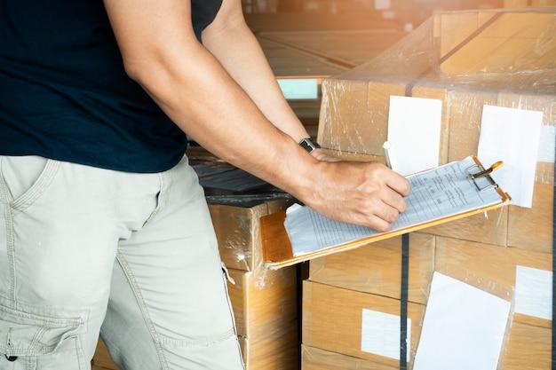 El trabajador está escribiendo una lista de verificación en el portapapeles para la gestión del inventario del almacén.
