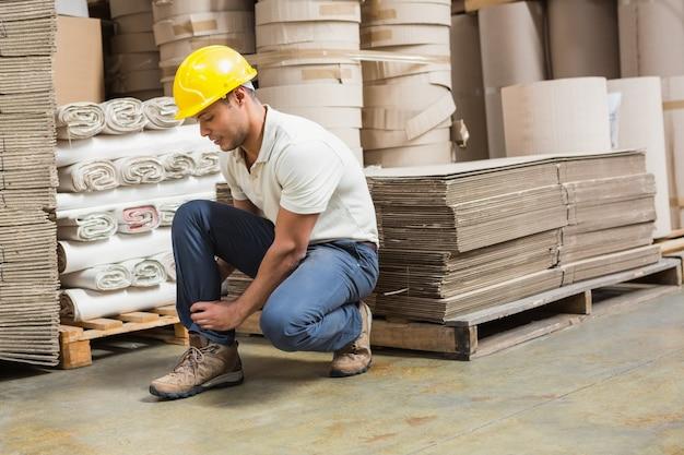 Trabajador con esguince de tobillo en el piso