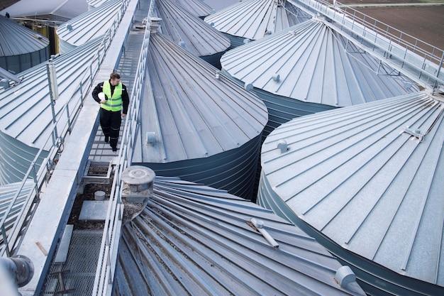 Trabajador de fábrica caminando sobre una plataforma metálica y realizando una inspección visual en tanques o silos de almacenamiento de alimentos industriales