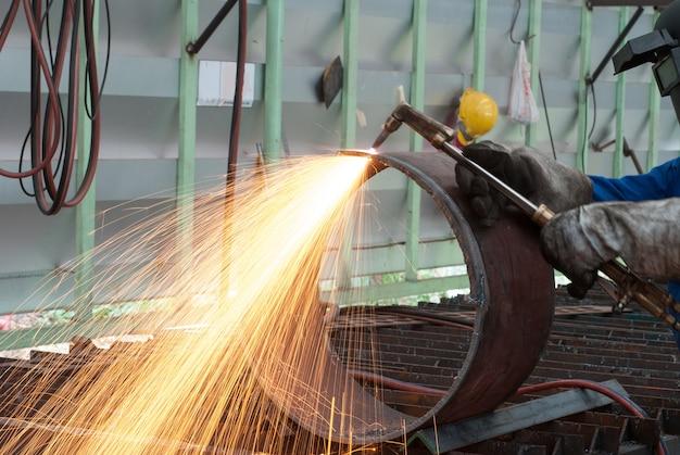 Trabajador en la fábrica de corte de tubos de acero con antorcha de metal
