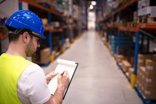 Trabajador de fábrica sosteniendo el portapapeles y comprobando el inventario del departamento de almacenamiento del almacén