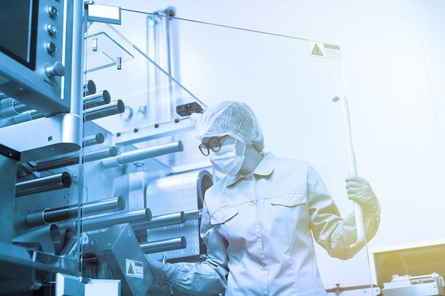 Trabajador de fábrica trabaja con máquina