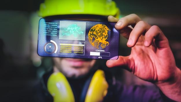 El trabajador de la fábrica utiliza un dispositivo de pantalla holográfica futura para controlar la fabricación