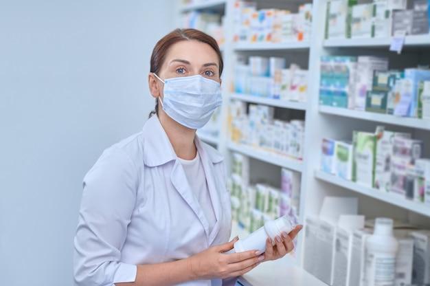 Trabajador de farmacia de pelo oscuro sosteniendo una botella de medicina de plástico