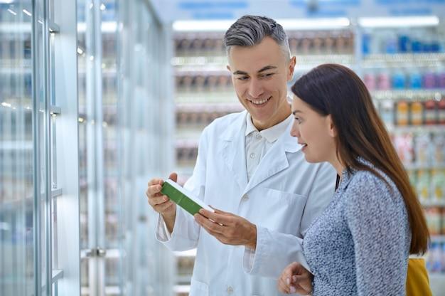 Trabajador de farmacia recomendando un nuevo medicamento a una clienta