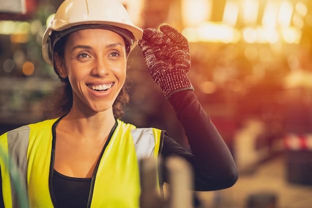 Trabajador feliz de la mujer afroamericana que trabaja la mano de obra de la sonrisa en la fábrica de la industria pesada con un buen concepto de bienestar.