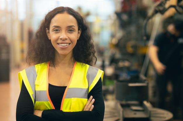 Trabajador feliz de la mujer afroamericana que trabaja la mano de obra de la sonrisa en la fábrica de la industria pesada con un buen concepto de bienestar