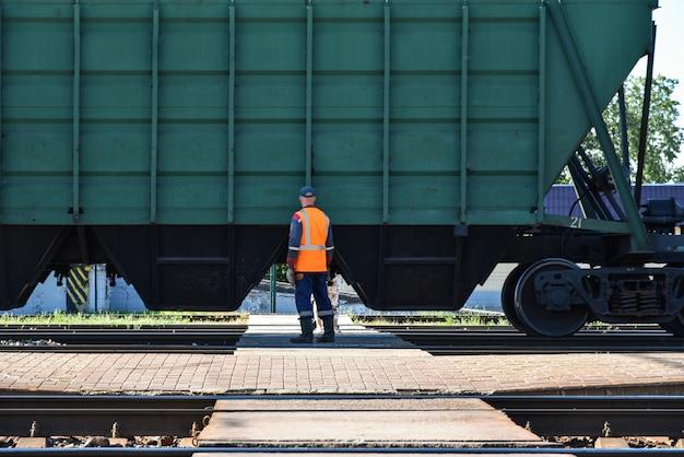 Trabajador ferroviario y personas que esperan el tren para pasar en el cruce del ferrocarril
