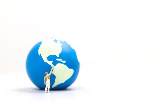 Trabajador de figuras en miniatura personas paintng mini mundo bola aislado sobre fondo blanco.