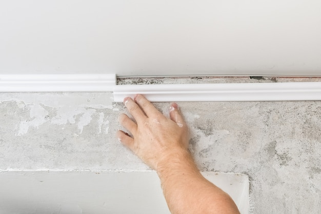 El trabajador fija la moldura de plástico al techo. instalación de cornisa de techo.