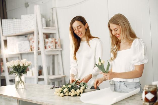 Trabajador con flores. la mujer hace un ramo.