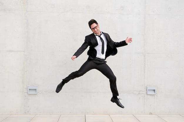 Trabajador con gafas y traje saltando