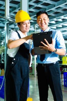 Trabajador y gerente de producción con portapapeles