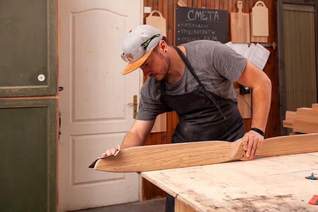 Un trabajador con una gorra y camisa pule el bloque de madera