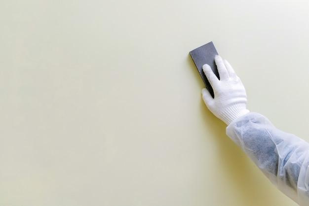 Trabajador con guantes y ropa de trabajo protectora lijando la pared.