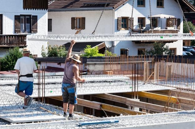 El trabajador guía la losa de hormigón descendente en el sitio de construcción.