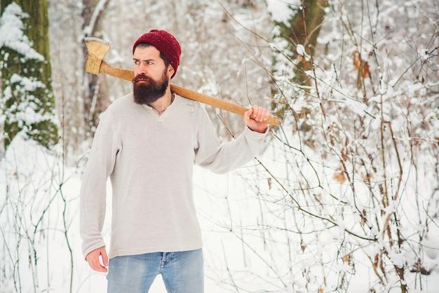Trabajador con hacha en el hombro en bosque nevado de invierno