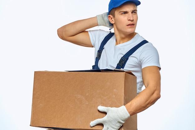 Trabajador de hombre con caja en manos servicio de carga de entrega trabajo fondo claro. foto de alta calidad