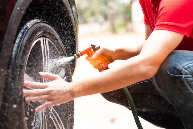Trabajador hombre lavando llantas de aleación de coche en el cuidado del automóvil.