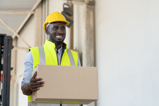 Trabajador de hombre negro en chaleco de seguridad y casco amarillo con caja de cartón preparando el producto para su envío en la fábrica de almacén
