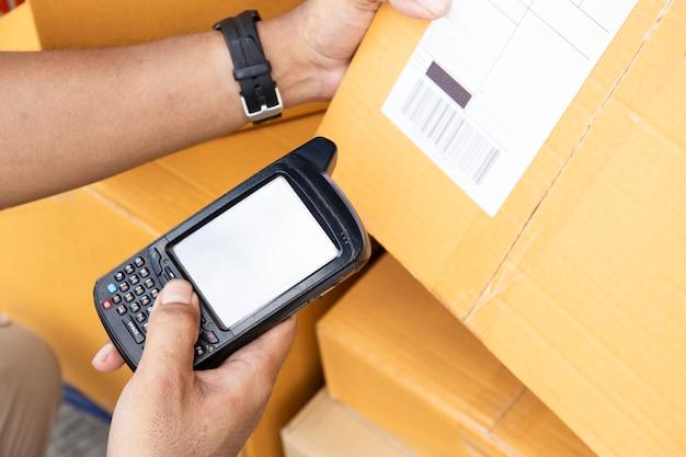 El trabajador del hombre está sosteniendo el escáner del código de barras con la exploración en los productos