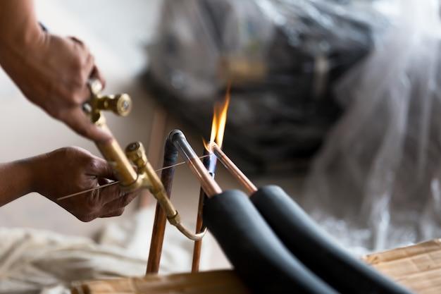 Trabajador de hombres del sistema industrial suelda la junta del acondicionador de tubo de cobre