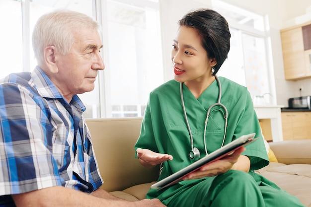 Trabajador del hospital visitando paciente senior en casa