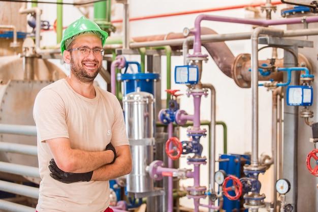 Trabajador de la industria feliz posando y sonriendo dentro de la fábrica con barras y tuberías alrededor