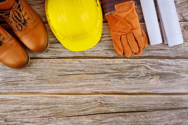 Trabajador de la industria ropa de trabajo protectora botas de seguridad guantes de cuero casco amarillo en arquitectos que trabajan con planos