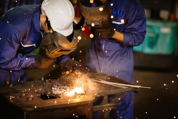 Trabajador de la industria tig soldadura de acero con máscara de seguridad para proteger la vista en la fábrica de metales.