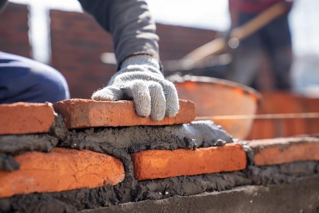Trabajador industrial albañil instalando mampostería de ladrillo con espátula en el sitio de construcción