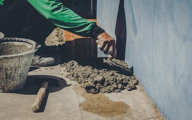 Trabajador industrial con herramientas de enlucido renovando casa.