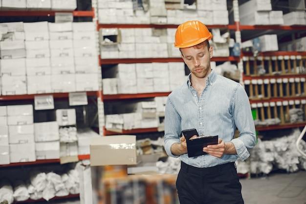 Trabajador industrial en el interior de la fábrica. hombre de negocios con casco naranja. hombre con camisa azul.