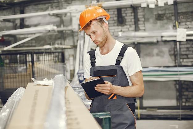 Trabajador industrial en el interior de la fábrica. joven técnico con casco naranja.